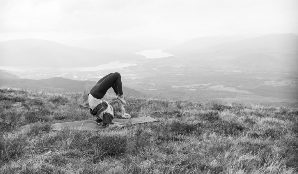 Woman practicing yoga in a field overlooking a valley